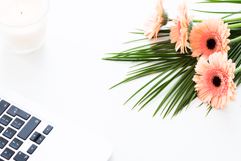A desk of blogger who works with Tailwind tribes, with flowers and a computer