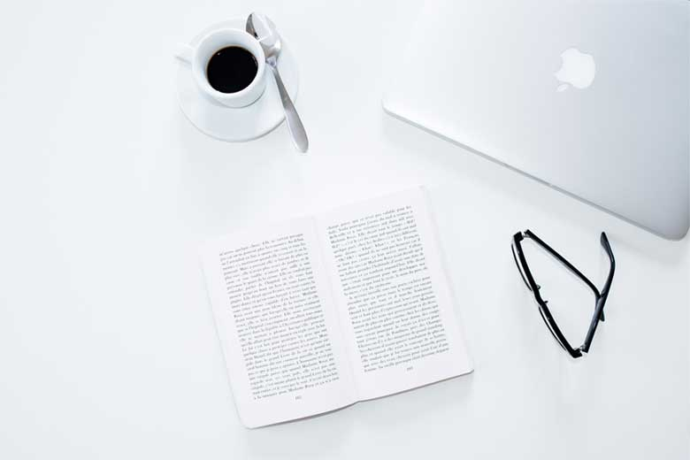 A cup of coffee, a book and glasses on a white desk
