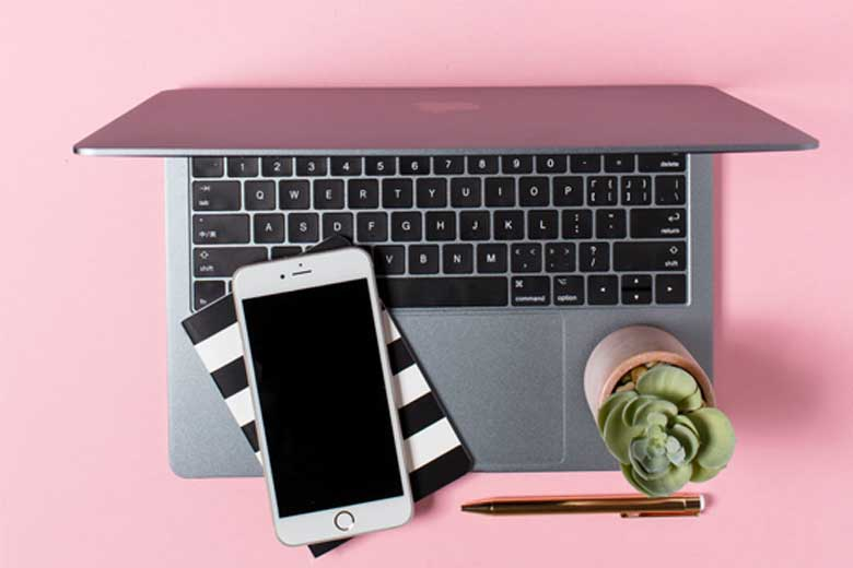 A laptop, mobile phone, and a cacti on pink desk