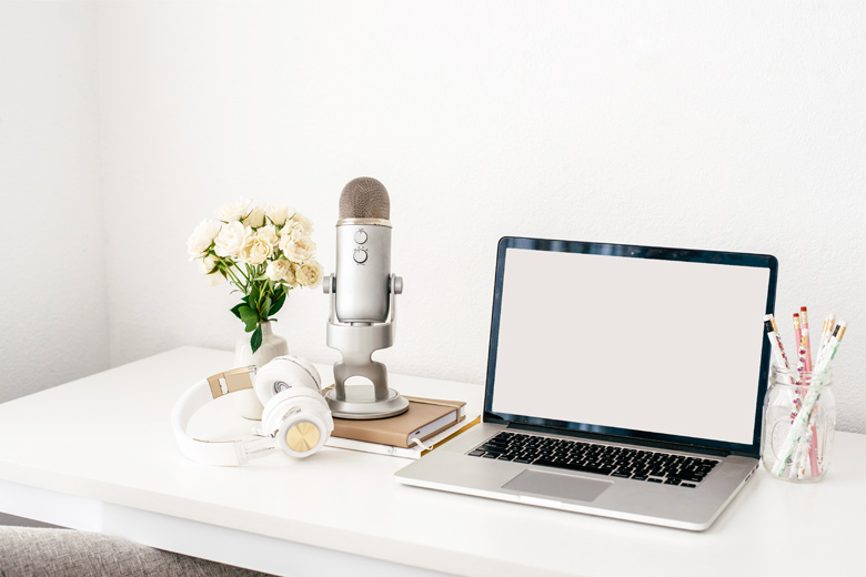 A desk with white roses, a microphone, and a laptop on it